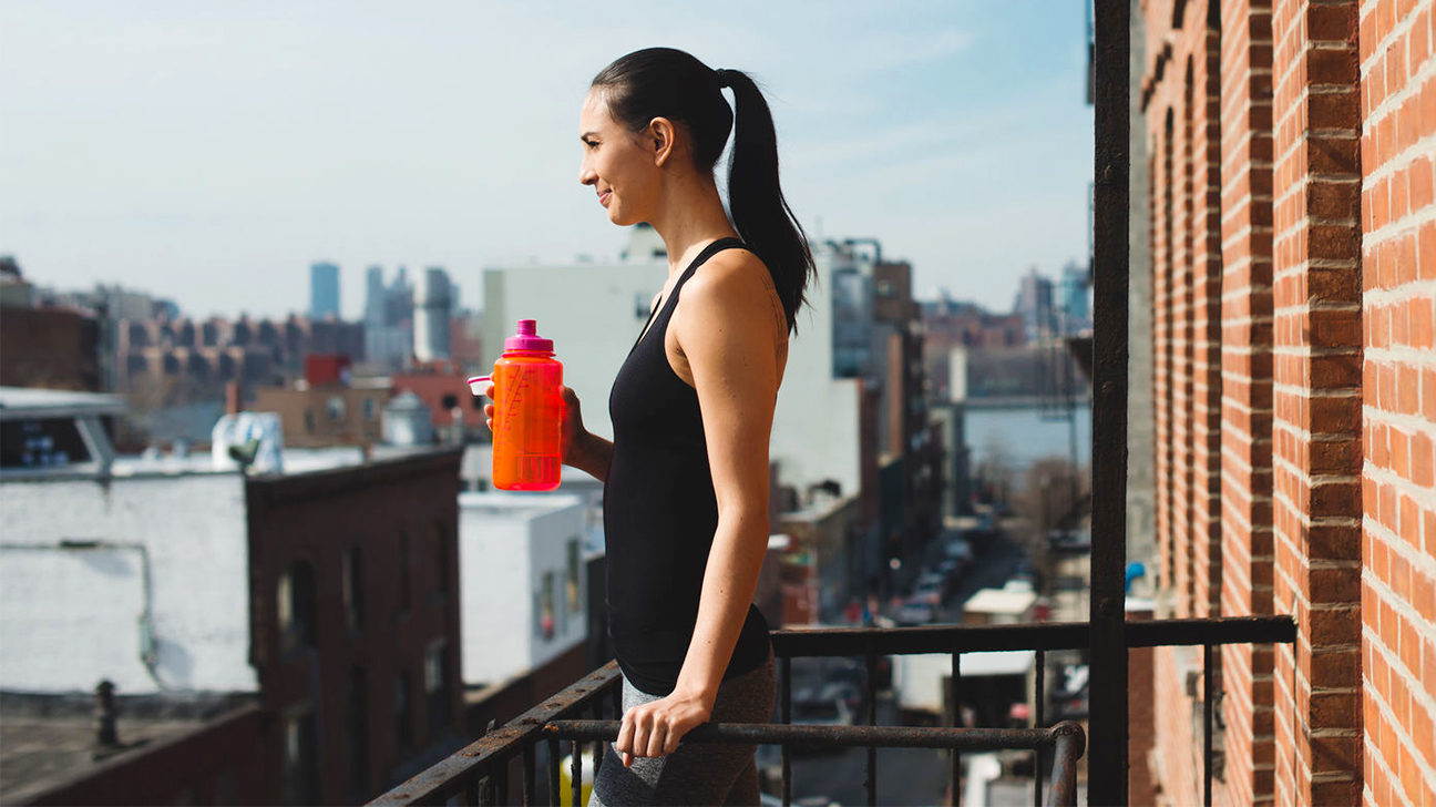 Female Athlete Drinking Water Before Workout